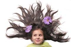 有被扇动的头发和花的小女孩 库存照片