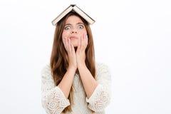 有被打开的书的滑稽的吃惊的逗人喜爱的女孩在她的头 图库摄影