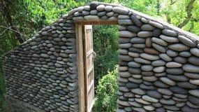 有被打开的老木门的石墙由路 石头墙壁在密林 从河的石头供水系统  库存图片