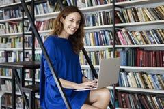 有被打开的膝上型计算机的年轻大学生妇女在膝盖,在键盘的手,运转或学会在图书馆,在共同工作的白天里 库存图片