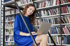 有被打开的膝上型计算机的年轻大学生妇女在膝盖,在键盘的手,运转或学会在图书馆,在共同工作的白天里 图库摄影