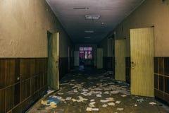 有被打开的门的黑暗的可怕走廊在被放弃的被破坏的诊所,透视 库存照片