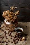有被按的花、咖啡和疏散烤咖啡豆的花瓶 免版税库存照片