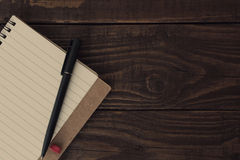 有被排行的纸的空白开放笔记本与在木桌上的笔 图库摄影