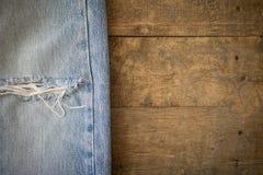 有被撕毁的纹理的老蓝色牛仔裤在木头 免版税库存图片