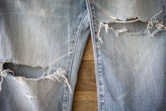 有被撕毁的纹理的老蓝色牛仔裤在木头 免版税库存照片