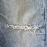 有被撕毁的纹理的老蓝色牛仔裤 库存照片