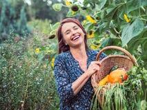 有被收获的菜篮子的笑的妇女  免版税库存照片