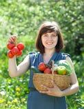 有被收获的蔬菜篮子的愉快的妇女  免版税库存图片
