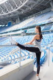 有被晒黑的皮肤的年轻运动的女孩在体育场内做一副横幅 妇女脱掉腿,做准备 库存照片