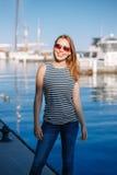 有被晒黑的皮肤的白种人白肤金发的妇女由湖岸海滨镶边了T恤杉和蓝色牛仔裤,与在背景的游艇小船 库存照片