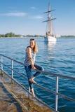 有被晒黑的皮肤的白种人白肤金发的妇女由湖岸海滨镶边了T恤杉和蓝色牛仔裤,与在背景的游艇小船 免版税库存照片