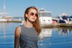 有被晒黑的皮肤的白种人白肤金发的妇女由湖岸海滨镶边了T恤杉和蓝色牛仔裤,与在背景的游艇小船 免版税库存图片