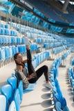 有被晒黑的皮肤的运动的女孩在体育场内做舒展坐位子 妇女脱掉腿,做温暖u 免版税库存图片