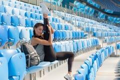 有被晒黑的皮肤的运动的女孩在体育场内做舒展坐位子 妇女脱掉腿,做温暖u 库存照片
