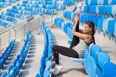 有被晒黑的皮肤的运动的女孩在体育场内做舒展坐位子 妇女脱掉腿,做温暖u 库存图片
