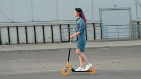 有被染的头发的可爱的年轻女人在乘坐反撞力滑行车的牛仔布礼服和白色运动鞋通过街道  影视素材
