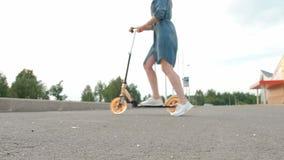 有被染的头发的可爱的年轻女人在乘坐反撞力滑行车的牛仔布礼服和白色运动鞋通过街道  股票视频
