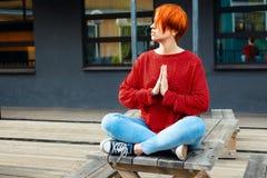 有被染的红色头发的成人白人妇女思考在与namaste姿态的木桌的 图库摄影
