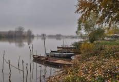 有被栓的小船的河在秋天11月灰色天 库存图片