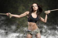 有被栓的胳膊的健身妇女有烟和军事短裤的 免版税库存图片
