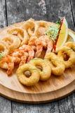 有被油炸的乌贼圆环、虾和洋葱圈的海鲜盛肉盘装饰用在切板的柠檬在木背景 库存照片