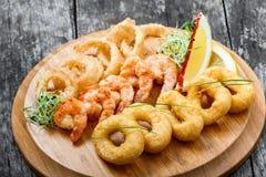 有被油炸的乌贼圆环、虾和洋葱圈的海鲜盛肉盘装饰用在切板的柠檬在木背景 库存图片