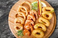 有被油炸的乌贼圆环、虾和洋葱圈的海鲜盛肉盘装饰用在切板的柠檬在木背景 免版税库存图片