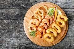 有被油炸的乌贼圆环、虾和洋葱圈的海鲜盛肉盘装饰用在切板的柠檬在木背景 图库摄影
