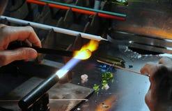有被点燃的气体火炬的玻璃剪裁工,当塑造玻璃时 免版税库存图片