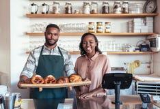 有被烘烤的物品的微笑的非洲企业家在他们的面包店柜台后 图库摄影