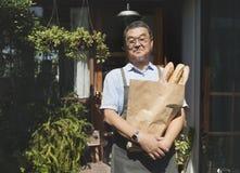 有被烘烤的物品纸袋的老亚裔人 库存照片