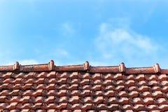 有被烧的瓦片的一个老屋顶 屋顶在反对蓝天背景的村庄房子里 库存图片
