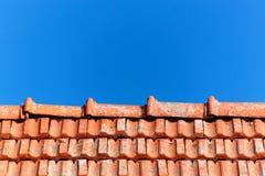 有被烧的瓦片的一个老屋顶 屋顶在反对蓝天背景的村庄房子里 图库摄影