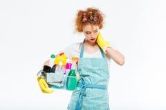 有被用尽的妇女拿着清洁物品和脖子痛 免版税库存照片