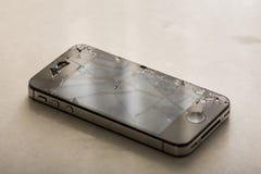 有被碰撞的lcd触摸屏的黑智能手机在白色大理石背景上 免版税库存照片