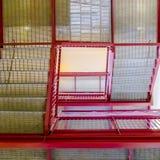 有被磨碎的从下面被观看的踩和明亮的红色扶手栏杆的台阶 免版税图库摄影