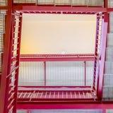 有被磨碎的从下面被观看的踩和明亮的红色扶手栏杆的框架方形的台阶 免版税库存照片