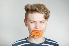 有被磨碎的红萝卜满嘴的英俊的男孩  库存照片