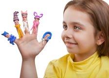 有被绘的人的愉快的女孩在黏土盖帽和被编织的围巾的手指的 免版税库存图片