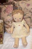 有被绘的眼睛和嘴的老被弄脏的布洋娃娃和被绣的searsucker围兜被扶植反对花卉被装饰的枕头- 免版税库存图片