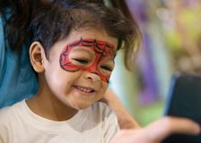 有被绘的面孔的亚裔孩子男孩作为蜘蛛 图库摄影