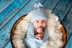 有被编织的帽子的小男婴在篮子,愉快地微笑 免版税库存图片