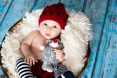 有被编织的帽子的小男婴在篮子,愉快地微笑 图库摄影