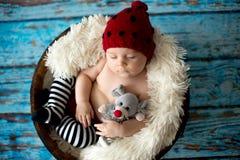 有被编织的帽子的小男婴在篮子,愉快地微笑 库存照片