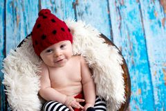 有被编织的帽子的小男婴在篮子,愉快地微笑 库存图片