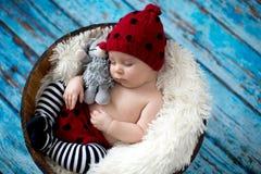 有被编织的帽子的小男婴在篮子,愉快地微笑 免版税库存照片
