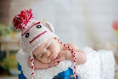 有被编织的帽子的小男婴,睡觉与逗人喜爱的玩具熊 库存照片