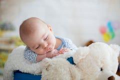 有被编织的帽子的小男婴,睡觉与逗人喜爱的玩具熊 免版税库存照片