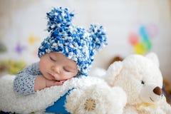 有被编织的帽子的小男婴,睡觉与逗人喜爱的玩具熊 免版税图库摄影